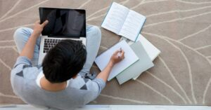 student working on laptop floor